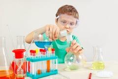 O rapaz pequeno em óculos de proteção de segurança estuda a prática química no laboratório Imagens de Stock