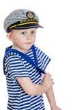 O rapaz pequeno em listrou a roupa de um marinheiro imagens de stock