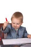 O rapaz pequeno em um terno de negócio assina originais imagem de stock