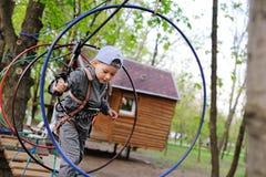 o rapaz pequeno em uma atração em um parque da corda passa um curso de obstáculo foto de stock royalty free