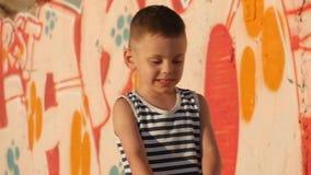 O rapaz pequeno em uma camisa listrada, que seja bonito fala e imagina o close-up video estoque