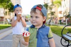 O rapaz pequeno encantador bonito come o gelado do copo da bolacha Imagem de Stock