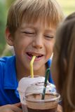 O rapaz pequeno engraçado bebe o milkshake Fotografia de Stock
