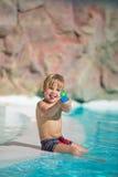 O rapaz pequeno engraçado joga com o brinquedo da água na piscina Foto de Stock Royalty Free