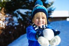 O rapaz pequeno engraçado tem o divertimento com snowglobe em um dia de inverno ensolarado Foto de Stock Royalty Free