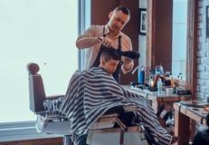 O rapaz pequeno engra?ado est? obtendo o corte de cabelo na moda do barbeiro expirienced no sal?o de beleza elegante do cabeleire foto de stock