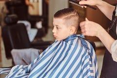 O rapaz pequeno engra?ado est? obtendo o corte de cabelo na moda do barbeiro expirienced no sal?o de beleza elegante do cabeleire fotografia de stock royalty free