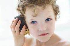 O rapaz pequeno escuta um despertador antigo Fotografia de Stock