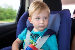 O rapaz pequeno está assentando no carro Imagens de Stock Royalty Free