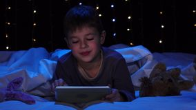 O rapaz pequeno está encontrando-se em uma cama que guarda um portátil e que olha uns desenhos animados Fundo de Bokeh filme