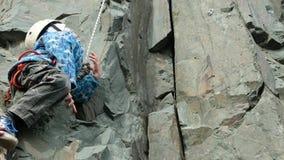 O rapaz pequeno está escalando às montanhas O atleta novo escala uma trilha de escalada filme