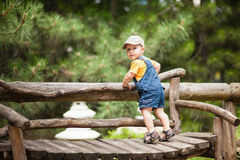 O rapaz pequeno está estando no banco fora Fotos de Stock Royalty Free