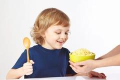 O rapaz pequeno está indo comer o papa de aveia do painço Imagem de Stock Royalty Free