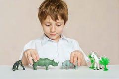 O rapaz pequeno está jogando com os animais do africano do brinquedo Infância Aprendendo o conceito imagem de stock royalty free