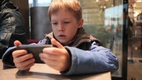 O rapaz pequeno está jogando com o telefone no café Menino louro com um telefone filme