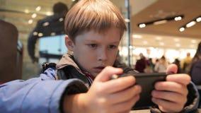 O rapaz pequeno está jogando com o telefone no café Menino louro com um telefone vídeos de arquivo