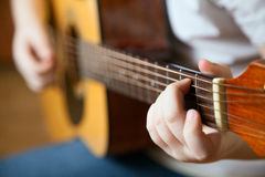 O rapaz pequeno está jogando a guitarra Fotografia de Stock