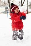 O rapaz pequeno está jogando na neve Foto de Stock Royalty Free