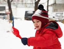 O rapaz pequeno está jogando na neve Fotos de Stock