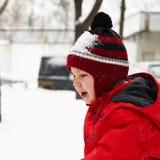 O rapaz pequeno está jogando na neve Fotografia de Stock Royalty Free