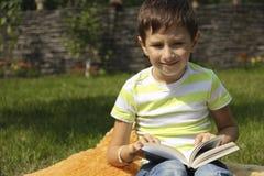 O rapaz pequeno está lendo um livro na grama Foto de Stock Royalty Free
