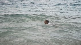 O rapaz pequeno está nadando alegremente no mar de adriático Ondas no mar Croácia filme