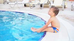 O rapaz pequeno está sentando a piscina no recurso video estoque
