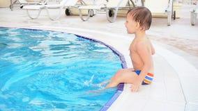 O rapaz pequeno está sentando a piscina no recurso filme
