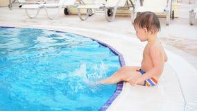 O rapaz pequeno está sentando a piscina no recurso vídeos de arquivo