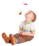 O rapaz pequeno está sentando-se em um fluxo com penas imagem de stock
