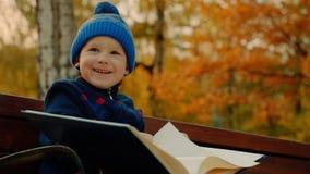 O rapaz pequeno está sorrindo com o álbum grande da família no parque do outono fotos de stock royalty free