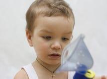 O rapaz pequeno faz a inalação. Imagem de Stock Royalty Free