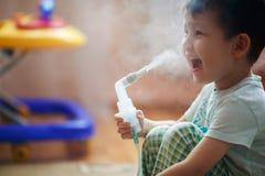 O rapaz pequeno faz a inalação em casa, tomando a medicamentação aos tubos brônquicos Fotografia de Stock