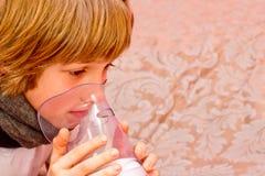 O rapaz pequeno faz a inalação em casa, tomando a medicamentação aos tubos brônquicos tube Fotografia de Stock Royalty Free