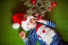 O rapaz pequeno feliz é mentiras perto do abeto Year& novo x27; feriados de s em um t-shirt listrado com Santa Claus imagens de stock