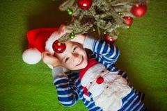 O rapaz pequeno feliz é mentiras perto do abeto Year& novo x27; feriados de s em um t-shirt listrado com Santa Claus imagem de stock