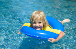 O rapaz pequeno feliz com anel de vida azul tem o divertimento no po nadador Foto de Stock Royalty Free
