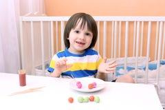 O rapaz pequeno feliz fez pirulitos do playdough e dos palitos em h Imagem de Stock Royalty Free