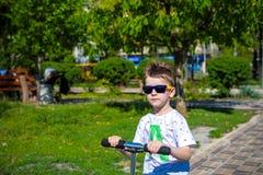O rapaz pequeno feliz monta o 'trotinette' na estrada no parque foto de stock