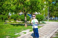 O rapaz pequeno feliz monta o 'trotinette' na estrada no parque fotografia de stock royalty free