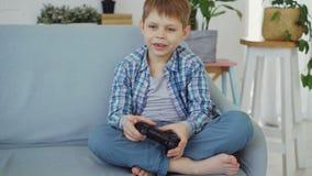 O rapaz pequeno feliz na roupa ocasional está jogando o assento sozinho do videogame no sofá em casa Tecnologias modernas, felize vídeos de arquivo