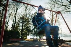 O rapaz pequeno feliz no balanço no dia de inverno bonito tem o divertimento Fotografia de Stock Royalty Free