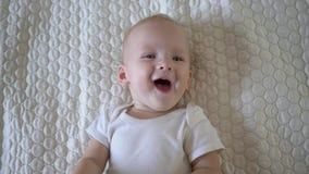 O rapaz pequeno feliz que encontra-se no fim da cobertura acima, bebê balança seus braços ao rir da câmera video estoque
