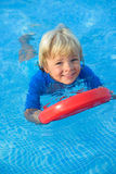 O rapaz pequeno feliz tem o divertimento com placa de flutuação na piscina Imagem de Stock Royalty Free