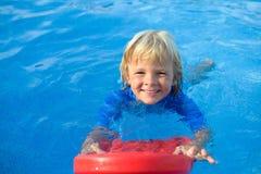 O rapaz pequeno feliz tem o divertimento com placa de flutuação na piscina Fotos de Stock