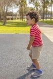 O rapaz pequeno focaliza em outras crianças com um olhar intenso fotos de stock