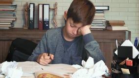 O rapaz pequeno frustrante cansado de seus trabalhos de casa amarrota seu papel video estoque