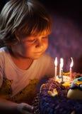 O rapaz pequeno funde para fora velas em seu aniversário imagem de stock
