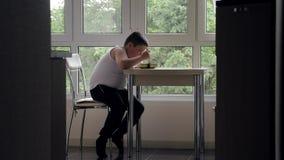 O rapaz pequeno gordo com fome senta-se na cozinha na tabela com apetite come a sopa no fundo da janela Conceito da medicina e da video estoque