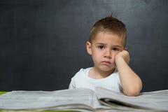 O rapaz pequeno gosta do homem de negócios no escritório com jornal Fotografia de Stock Royalty Free
